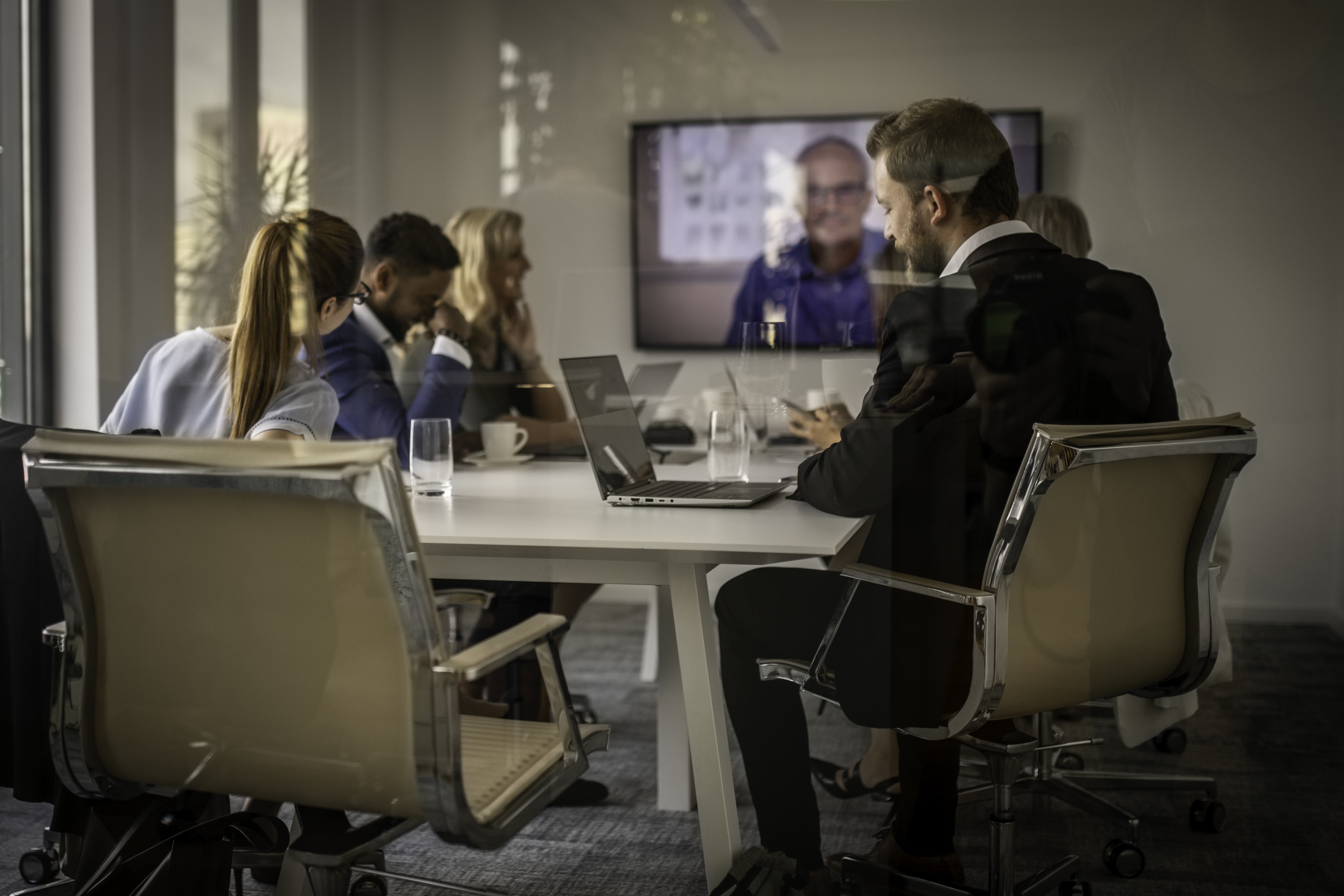 Business people having a meeting and a video conference in a modern office conference room.