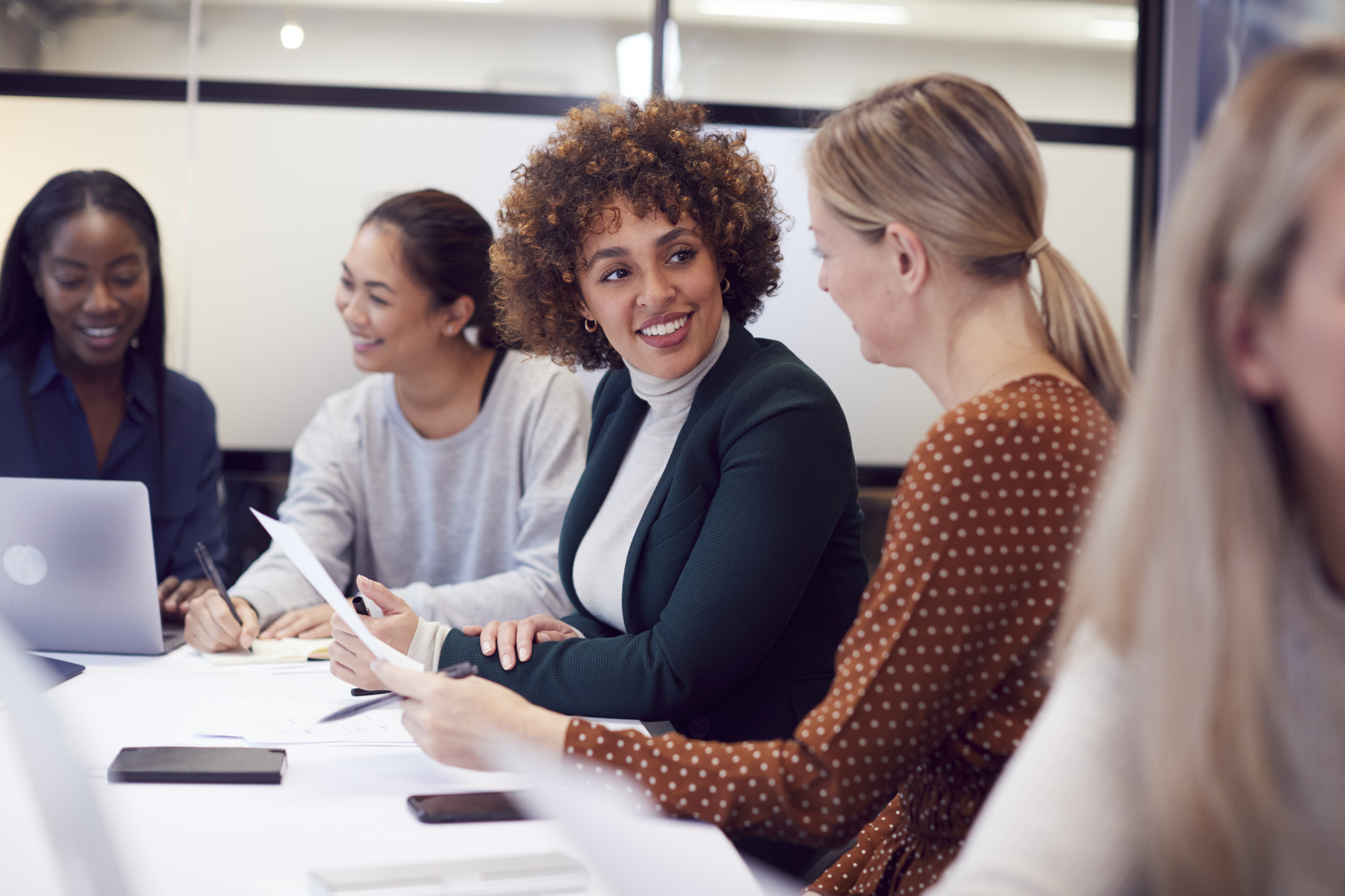 Group Of Businesswomen Collaborating In Creative Meeting Around Table In Modern Office